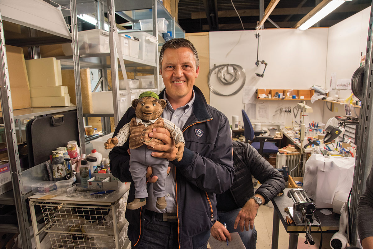 KINOMAGASINETs Fredrik Olsen Hagstrøm, som selv er stor Egner- fan, synes det var ekstra stas å ta og føle på selveste Bamsefar. Det er en av de tyngste og dyreste dukkene i produksjonen, og koster opp mot 250.000 kroner. Foto: Per Mork, KINOMAGASINET.no©