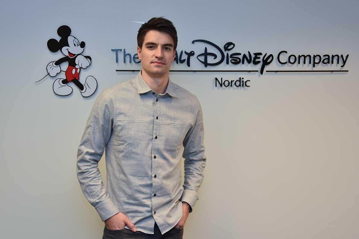 Ludvig Andreas Johansen mener den norske kinobransjen er «litt som en stor familie.» Her ved Disney-logoen på Skøyen-kontoret i Oslo i januar 2017. Foto: John Berge, KINOMAGASINET.no ©